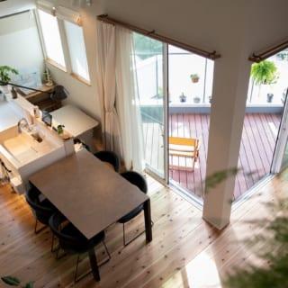 2階LDK。窓越しの三角形のスペースがテラス。L字のリビング(写真右)とダイニング(写真左)をつなぐようにテラスがあり、LDKTと呼びたくなるほど内と外の一体感が高い。壁は珪藻土、床は無垢の杉材。テラスからの陽光で、自然素材のナチュラルな上質感が引き立つ