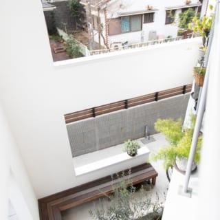 2階テラスから庭を見下ろす。吹抜けのおかげで1階の庭との一体感がとても高い。庭を囲む壁や柱は屋根まで伸びているので2階テラスもほどよく囲われ、プライベート感がある