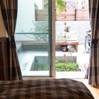 主寝室から庭を見る。主寝室と子ども室は庭を介してはす向かいの配置。どちらも庭の爽やかな光や外気を取り込めるうえ、庭越しにお互いの気配がわかる一体感も生まれている