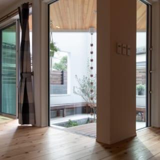 玄関を入ると、白壁でほどよく囲われた明るい庭が目の前に広がる。間取りはできるだけシンプルにし、収納も過度に設けなかったことで空間に余裕が生まれ、玄関ホールもゆったり