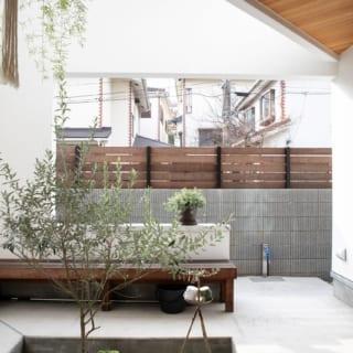 白壁とコンクリート床の庭にはウッドベンチも。リゾートホテルのテラスのような空間で心地よくくつろげる