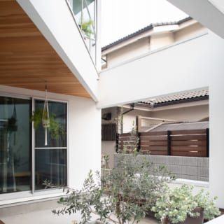 住居とひと続きの壁や柱で囲まれた庭は頭上半分が2階テラス(写真左上)。もう半分は吹き抜けている