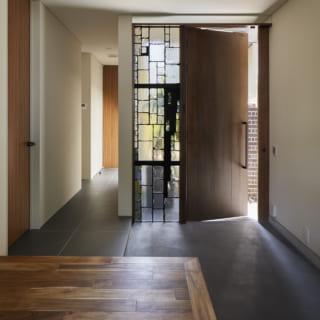 1階玄関。玄関ドア横の幾何学デザインのステンドグラスは、Nさまが作家にオーダーしてしつらえたもの