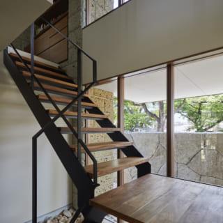 階段沿いは上下とも大きな窓で開放感たっぷり。階段下には外構と同じ石を敷き、外とのつながりを演出