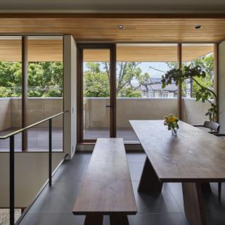 北の並木道に面した2階ダイニング。余計な壁を残さず美しくはめ込まれたガラス窓の向こうには、広いデッキと並木道の緑。デッキの軒天と同じ木材が室内天井まで張り出して外とのつながりが強調され、ダイニングそのものが大きなデッキのように思える気持ちのよい空間だ