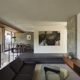 2階リビングからダイニングを見る。絵が飾られた壁の向こうがキッチン。右の壁にはアクセントとして大谷石が張られ、モダンながらも高級感のある空間となった。2階はスキップフロアでリビングが一段低く、ホッと落ち着ける雰囲気。左は大きな窓と吹抜けの階段で、抜群の開放感