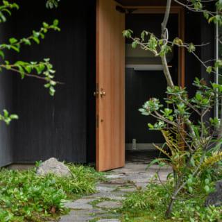 芝生を貼った庭から玄関まで乱石張りのアプローチが続く。敷石に使用したのは、砕石を砕く前の石。目地はコンクリートなどであえて固めていないため、苔生し草も生える。それも楽しい