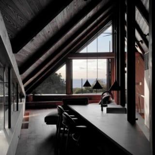 2階、玄関を入ると驚くほどに開放的な室内空間が広がる。三角形の家のフォルムに合わせてダイニングテーブルも三角形にすることで、室内を効率的に使用。室内は海をより印象的に見せるよう若干暗めに計画。陰影も美しい空間は、非日常感たっぷり