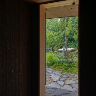 アプローチに使用した石を通り抜け土間にも敷き詰めた。同じ素材を用いることに加え、高さのレベルを合わせることによって家の外と内が緩やかにつながり一体感が生まれた。通り抜け土間の天井と軒天の素材も、同じラワン合板でまとめている