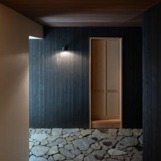 玄関(写真右側/南)とサービスヤード(同左側/北)をつなぐ通り抜け土間。壁は外壁と同じく杉板に塗装を施している。天井と軒天のラワン合板には、撥水性や耐UV性、防腐性などに優れた塗料「ノンロット」を塗装。写真正面は父親の部屋となる離れ