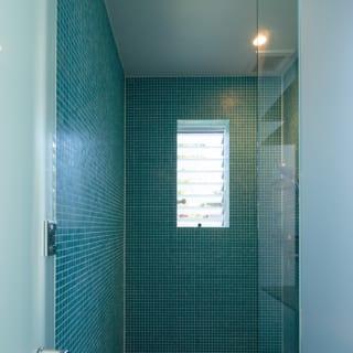 シャワー室は、海をイメージしたグリーンのモザイクガラスタイル張り