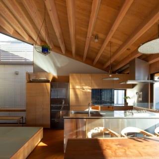 2階リビング側からダイニング、小上がり、キッチンを見る。畳敷きの小上がりは中心に掘りごたつを隠し、その周りは収納とした。キッチンは背後にパントリーがあるほか、リモコン類も目につかないよう収められている。ワークトップにも棚を設け、見た目以上に収納力がある空間だ
