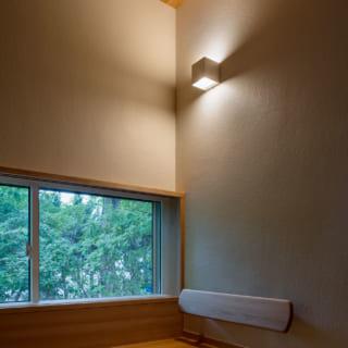 母親が使う茶の間。漆喰に土と藁すさを混ぜた塗り壁、天井は無塗装の杉板。南側には低めの腰窓を設え、床に座るとちょうどいい高さに。写真右側には3畳弱の納戸を設けた