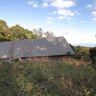 道路側からはほぼ家の屋根のみが見え、プライバシーを確保。画像左側にある玄関から海に向かって屋根が上がり、内部空間も同じように広がっていく