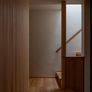 """1階と2階をつなぐ階段には、トップライトからやわらかい光が降り注ぐ。階段はいわば2階の玄関。光の明るさと温かさが、1階の両親やゲストを""""迎え入れる""""雰囲気を醸し出している"""