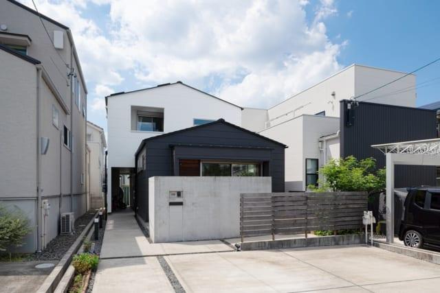 手前から木製の柵、コンクリート塀、ガルバリウム合板外壁の建物部分、サイディングの建物部分と、あえて素材を変えて段違いに配置してリズム感を生み出している。木製の柵、コンクリート塀と二重にしたのは、道路からの視線を遮るという役割もふまえている