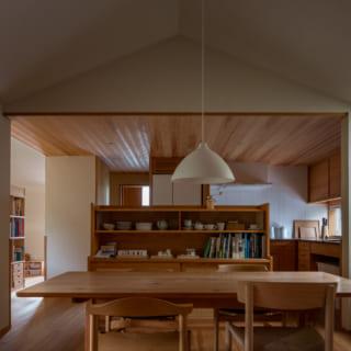 リビングから見る2階のLDK。キッチンとリビングの間に位置するダイニング空間は、屋根の形状を活かした高い天井が特徴。リビングとキッチンは逆に天井の高さを抑えている