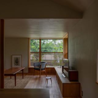 """ダイニングから見るリビング。壁も天井も土とスサ入りの漆喰仕上げだが、天井部分は素材の配合やコテの押さえ具合を調整し、やや光沢のある仕上がりに。小学校に面したコーナー窓の下部にはルーバー網戸を設置。外を完全にシャットアウトするのではなく、程よい目隠しとなっている、その""""塩梅""""が見事だ"""
