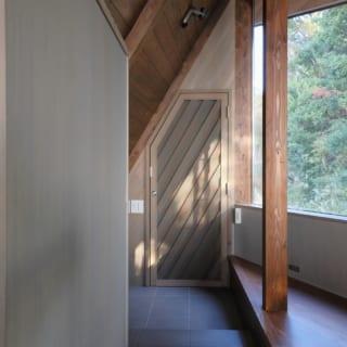 玄関扉は、網戸を内側に設け2重扉にした。網戸は斜め格子に網を張り、さらに鍵もつけたことで安心して扉を開け放せる。玄関からは壁に沿ってタイル張りの通路を設置。テラス側の階段まで伸びており、通り土間のように使える