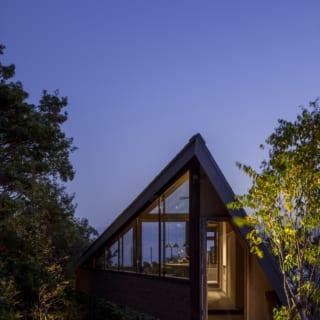 三角形のフレーミングがより美しい夜の風景。庭の木々にもほんのり照らす程度の照明を設置