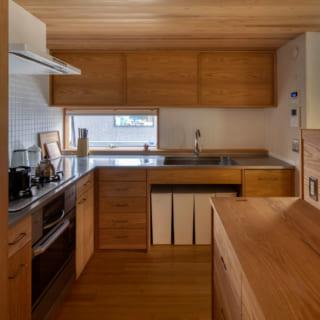作業性と動線を考慮し、L型のキッチンを採用。ダイニングとの境界には低めの収納棚を設置。キッチンで調理しつつもリビングの様子が何となく伝わる、程よい距離感がいい。シンクとコンロはステンレストップで、建具の木部はレッドオークを使用。タイル、目地ともに白でまとめたのは、掃除のしやすさを考えてのこと。目地幅もあえて広くし、油などで汚れたときでもタイルと目地を一度に漂白することができる