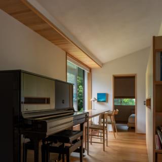 LDKから寝室へ続く廊下。子供たちのピアノの隣が箕輪さんのワーキングスペースとなっている。窓の明かりが壁と天井に光のグラデーションを描き、正面奥にある寝室の陰影とあいまって、実際以上の奥行きを感じさせる