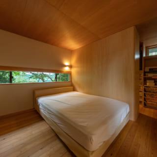 2階主寝室。天井はラワン合板、壁はシナベニア合板。ゴルフ練習場側の南面窓は、寝室なので心地よくお昼寝ができてストレスなく本が読める程度の光がいいという考えから、光の調整とプライバシーを兼ねた横スリット窓に。天井も低めに抑え、落ち着いた空間となっている。寝室の奥には3畳ほどのウォークインクロゼットを配置