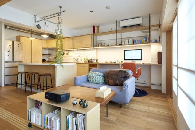 リビングからキッチンを見る。奥の壁面、左から始まるキッチントップと鎌松さんのデスクは継ぎ目なく繋げた。同じように上の棚も繋がっている。吊り棚や、左壁面に見えるパントリーとして使用する棚まで梁下の同じ高さで揃え、抜けをつくったことで広々とした空間が強調される
