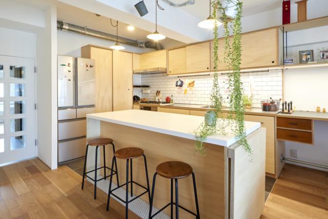 キッチン。「カウンターの高さやコンセントの位置のほか、調理器具の収納棚の位置まで身長に合わせてつくってもらえたので嬉しい」と奥様。キッチンタイルは目地が濃くクールなものを、椅子の下の床面にはヘキサゴンタイルをアクセントに配置し清潔な印象の中にビンテージ感も漂う
