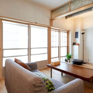 リビングの窓側にあるこのスペースはあえて使い方を固定しない余剰空間。「余白がある空間は便利だし、ゆとりが生まれる」と鎌松さん。画像右上部のガラスと、窓の建具はいただいてきたもの。障子のように見えるのはポリエステル製の寒冷紗。天井や壁は友人たちと皆で白く塗った