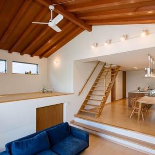 リビングは梁見せの勾配天井にすることで高さを出し、さらにダウンフロアリビングにすることで、空間をより広く感じられるようにした。リビングの床から天井までは最高部で約3.6mある