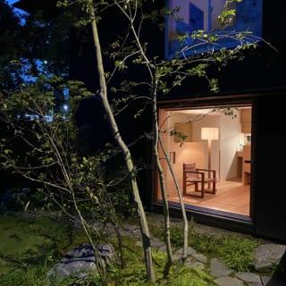 アプローチから見る夜のワンシーン。1階リビングから漏れる明かりが庭の木々を照らす。椅子に座ってくつろぐ、縁側のようなイメージ
