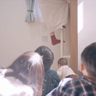 1階子ども室からタラップで中2階のロフトへのぼる様子を、興味津々に眺める家族。遊び心のある設計が、家族のコミュニケーションも生んでいる