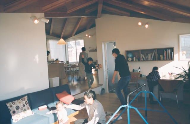 2階LDKの来客時の様子。段差で遊ぶ子ども、カウンターデスクの子ども、ソファで赤ちゃんをあやす大人、奥のダイニングで食卓を整える奥さまたち。ダイニングとリビングが少しずれてつながる設計や造作家具のおかげで、同じ空間にいても各人が自由に過ごせる居心地のよさがある