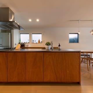 キッチンはオーダーメイドのアイランドキッチン。面材もリビング天井と素材を合わせ、ラワン材を採用することで、LDK空間全体でデザインに統一感をもたせている。すぐ横には、I様の要望でもあるパントリー収納も設置