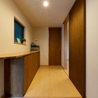 玄関ホール。下駄箱は、リビングの天井やキッチン面材などと同じラワン材で統一している