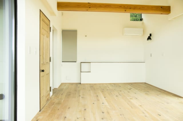 3階にあるご主人の個室。正面の壁にはニッチ棚のあるベッドヘッドを設置。天井の木材は構造の梁。T邸のLDKや個室は梁を現しで仕上げ、木の質感を楽しめるようにしている。出入口の扉はイギリスのアンティーク建具