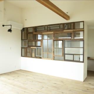 3階にあるお子さまの個室。仕切り壁に使った小さな窓は全て、奥さまがご自身で買い集めた日本の古民家のもの。シンプルな空間にレトロな魅力を添えている。この仕切り壁の奥は大きなウォークインクローゼット。写真右にはパソコン作業などができるカウンターデスクもある