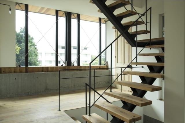 2階の階段まわり。RC造の1階天井はコンクリート梁が上に出る逆梁にし、2階の窓下の壁としてデザインに取り入れた。写真奥のLDKへの扉はイギリスのアンティーク建具。木板と鉄筋棒を組み合わせた階段も洗練されている。この写真の右手に行くとエレベーターホール