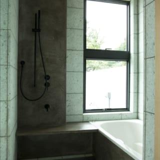 2階浴室。壁は水に強く意匠性も高いモールテックスと十和田石。床は十和田石。洗い場からテラスに出られる