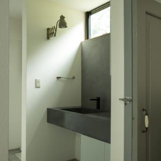2階洗面室。この先に洗濯機置場と浴室、手前にはキッチンがあり、家事動線がとてもよい。洗面台のブラケットライトはTさまがおもちだったアンティーク。写真右の引き戸はフランスのアンティーク建具