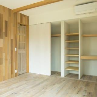 2階にあるお子さまの個室。ここも、床はアンティーク風に仕上げたホワイトオーク、壁は白ペンキで統一している。写真左の壁は色の濃淡が異なるレッドシダー材。出入口の扉はアンティーク建具