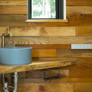2階トイレの手洗い。カウンターの木板と水栓はアンティーク。アイアンのペーパーホルダーは作家に依頼したオーダー品