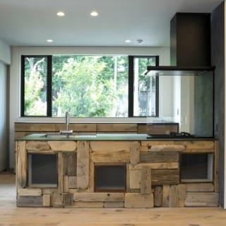 2階LDKのキッチン。カウンターの前面には、奥さまが集めた大小さまざまの流木を張っている。流木ならではの丸みや深みのある温もりが印象的で、LDKの顔ともいえるほど表情豊か。背後には裏山の緑が広がり、気持ちよく料理ができる