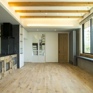 2階LDKをテラス側から見る。写真正面にはガラスのアンティーク扉を飾りとして入れてあり、階段を行き来する家族の様子を感じ取れる。アンティーク材を多用しているが、床はホワイトオーク、壁は調湿効果のある白ペンキで統一。ほかの素材の種類を抑え、全体をまとめている
