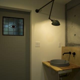 1階水まわりの洗面スペース。モールテックスの床や壁にアンティーク材が映え、シックで洒落た雰囲気