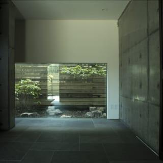 1階エントランスホール。玄関を入ると正面に腰高の大きな窓。コンクリート打ち放しで仕上げたシックな空間だが、視線が抜けて裏山の緑も見え、空間の心地よい広がりを感じさせる