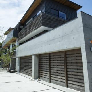 写真手前、1階ビルトインガレージの手動引き戸は木板で製作。コンクリート壁と相性がよく、モダンな印象に