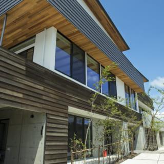 南の外観を西側から見る。軒裏に張った木材はレッドシダー。T邸は建物の中心に住空間があり、1階はその両脇にビルトインガレージを配置。贅沢な広さがあり、愛車やジェットスキーの手入れもゆったりと行える。それぞれのビルトインガレージの上は、広々した2階のテラス