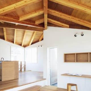 2階リビングからダイニングを見る。連続する2つの山形天井が、住宅の屋根が連なる外部の景色とリンクする